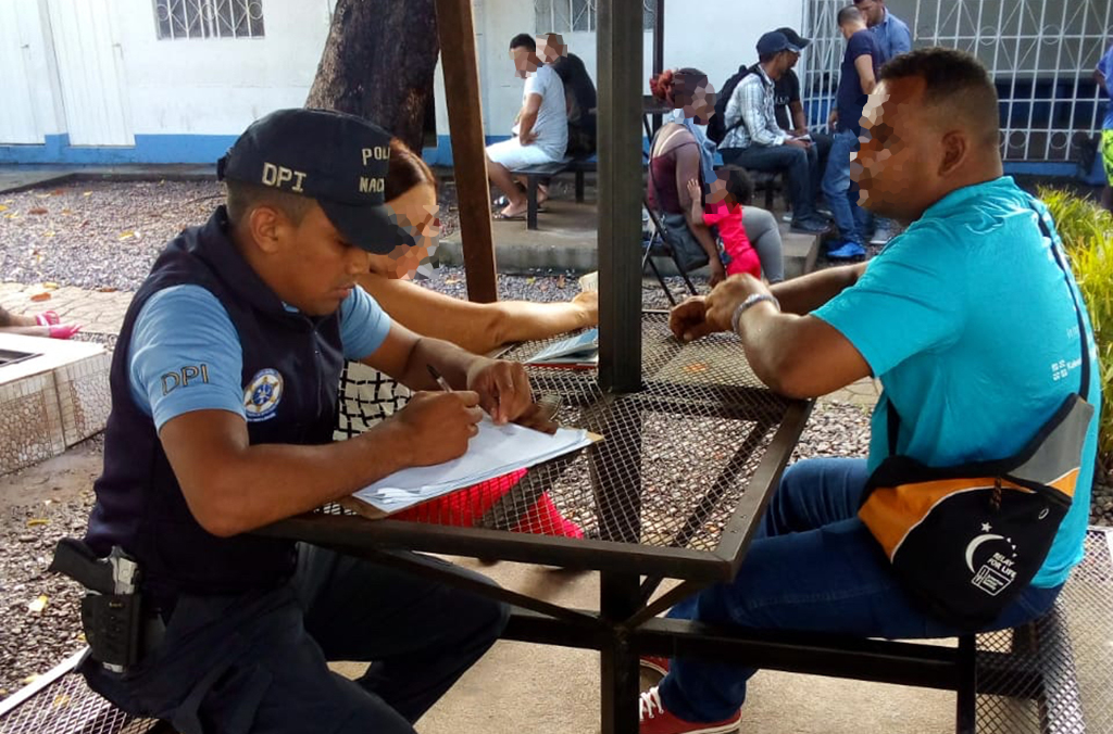 Police speak to migrants in Honduras.