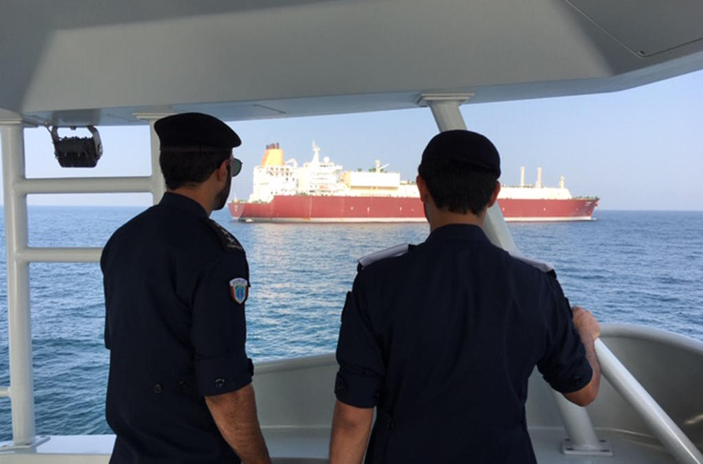 Qatari Coast Guard Officers monitor nearby vessels for signs of illegal discharge